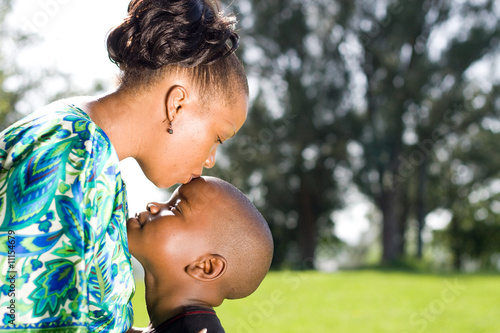 african mother kissing her child boy