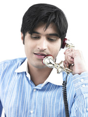 asian guy talking on an ornate phone