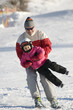 Father and daughter skiing together on mountain.