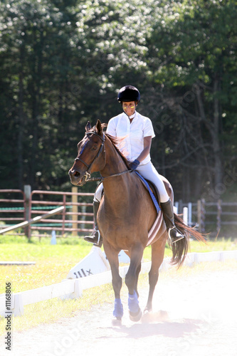 black teenage girl riding her horse in the ring