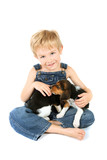Young boy sitting with Beagle puppies on his lap poster