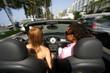 Jeune couple conduisant une voiture décapotable