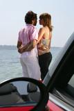 jeune couple face à la mer devant une voiture décapotable