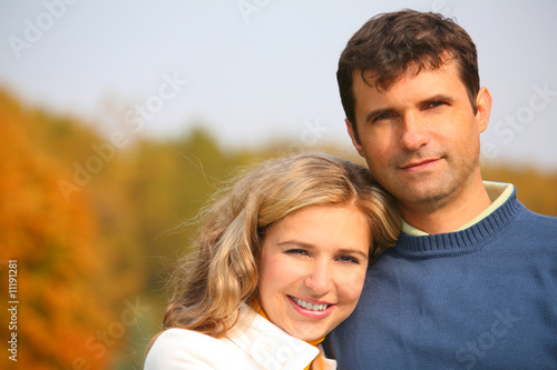 The husband embraces the wife in autumn park