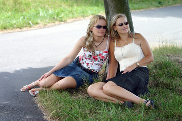two girls at the tree with sunglass