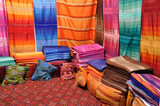 Colorful fabrics and cushions for sale in Fes, Morocco poster