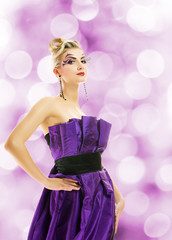 Beautiful woman in purple dress over abstact blurred background