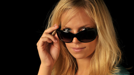 Beautiful woman with blonde hair looking over sunglasses.