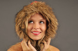 Beautiful woman with furry hood smiling and looking upward. poster