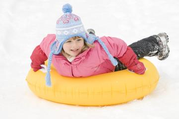 Little girl sliding on innertube on snow