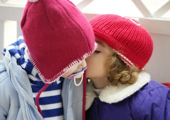 Children, winter red hat whispering in ear