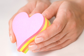 Hands holding heart shaped colorful sticky notes