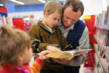 Grandfather and grandson and girl read the book in bookshop