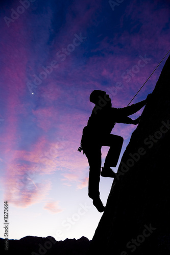 Rock climber clinging to an overhang.