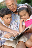Grandfather and kids reading book