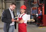 boss talking to worker in uniform in factory poster