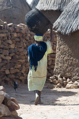 woman carrying iron cooking pot