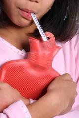 bambina con termometro e borsa acqua calda