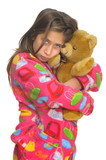 Beautiful young girl in pajamas posing with teddy bear poster