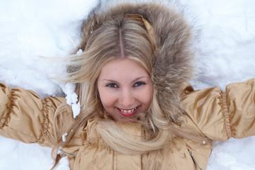 Winter girl is lying on snow