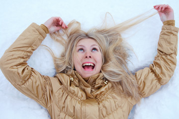 Crazy Winter girl is lying on snow