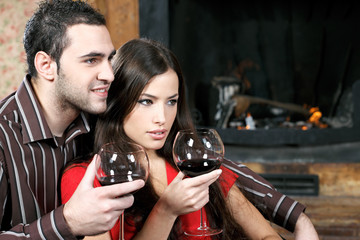 Close up of a young couple in love enjoying wine near fireplace