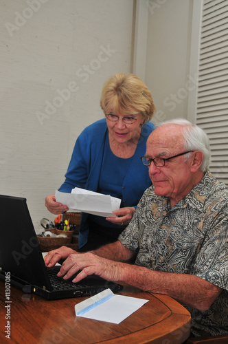 Senior couple pay bill on Internet