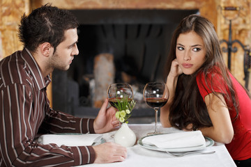 She feels bored with him. Couple's table near fireplace