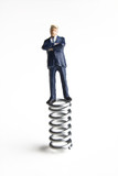 Businessman figurine standing on a spring