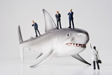 Business figurines placed with a shark figurine.