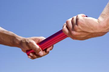 Close up of men passing relay race baton