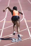 African female runner leaving starting block on race track
