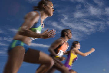 Low angle view of female athletes running in race