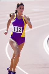 Female athlete running on race track