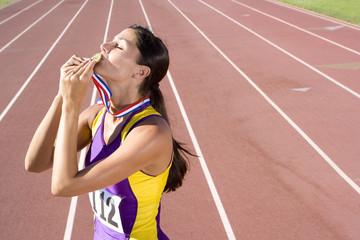 Female athlete kissing gold medal on race track