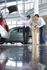 Salesman showing car to customer