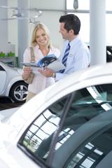 Car salesman talking to female customer