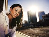 Pretty woman at sundown in city poster