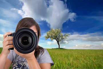 young female photographer with digital photo camera shooting lan