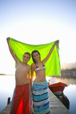Teenagers holding towel on dock