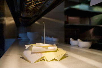 Restaurant receipts stacked on spike
