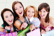 Group portrait of laughing girls with shopping bags