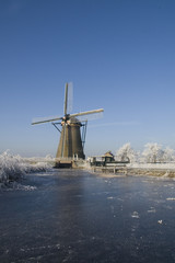 Frozen river with windmill in Holland