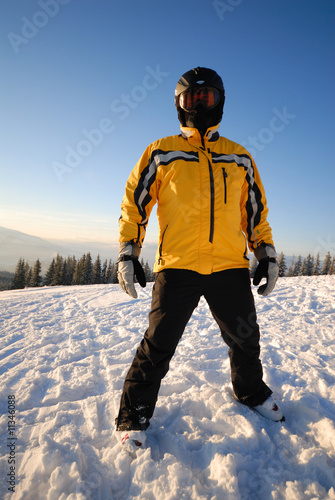 Skier dressing yellow coat in a black helmet