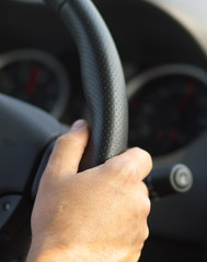 Man's hand on car steering close, black, vertical