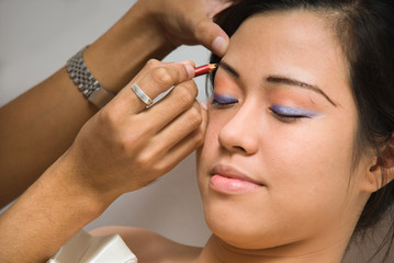 Asian girl receiving eye-liner make-up