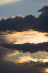 Sun setting behind clouds in sky
