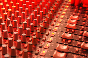 music soundboard under red stage lighting