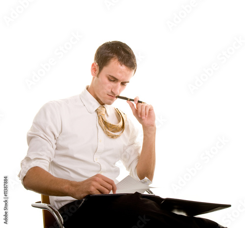 Young Man Sitting in Chair Looking at Notes
