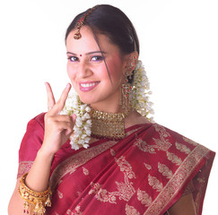 Teenage girl in red sari showing two fingers